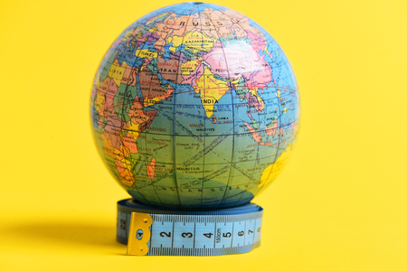 parallels: Globe with visible asian part in the middle, standing on a roll of measuring tape isolated on bright yellow background