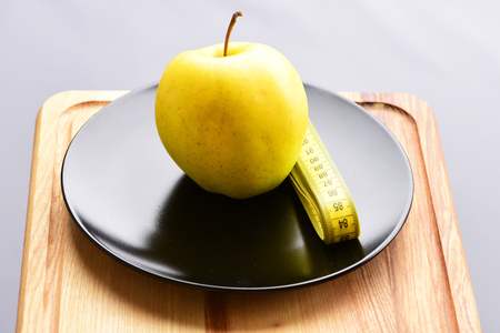 Apple lying on shiny black ceramic plate near neatly folded yellow sewing centimeter standing altogether on vintage wooden cutting board for kitchen isolated on light grey background