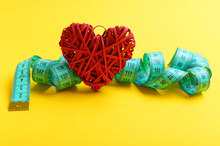 Measuring tape curled all over and tied around red decorative heart, isolated on yellow background, copy space