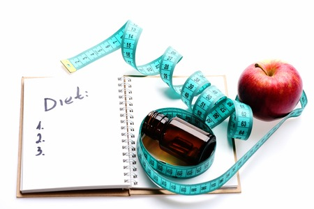 Plan for health. Tape for measuring in blue color twisted around red apple and brown glass bottle lying on open notebook with written note isolated on white background. Regime and healthy food concept Stock Photo