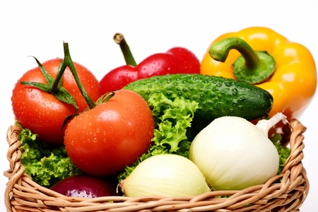 close up of onions in a basket: fresh vegetables concept, green lettuce leaf, tomatoes with onions, peppers, cucumber in basket isolated on white background, close up