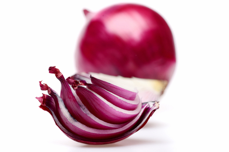 Sliced red onion quarter in close up and whole purple vegetable behind it isolated on white background, selective focus. Beauty in food Stock Photo