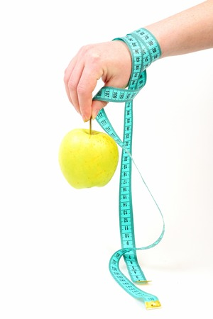 Concept of fruit diet, vitamin nutrition and health. Hand with green apple and cyan measuring tape, which ties around wrist, isolated on white background