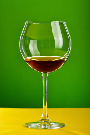 Glass of brown alcoholic beverage standing on yellow surface on green background. Minimalistic festive concept