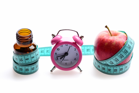Measuring tape in cyan color ties around glass bottle and red apple with pink alarm clock located between them, isolated on white background Zdjęcie Seryjne