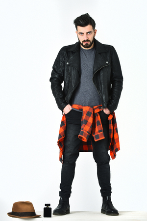 Bearded man, short beard. Caucasian serious hipster with moustache standing near perfume bottle and hat wearing black leather jacket, checkered red shirt and ripped jeans isolated on white background Stock Photo