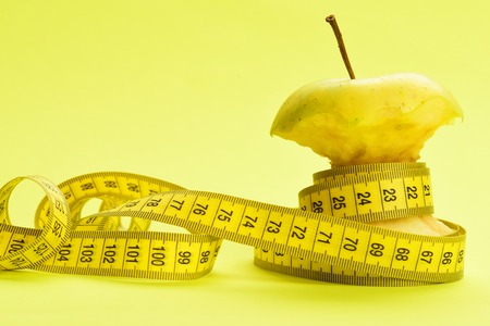 Tape for measuring wraps around bitten apple on warm yellow surface with copy space. Dietary concept