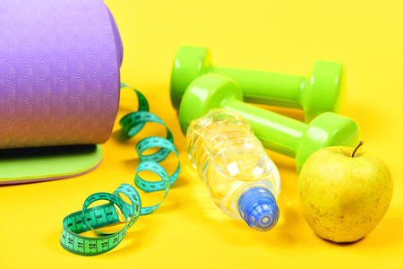 Concept of healthy lifestyle with purple yoga mat and couple of dumbbells, twisted measuring tape near juicy green apple, bottle water isolated on yellow background, close up. Body shaping and sports