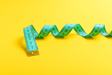 Concept of fitness and slim shape with turquoise twisting measuring tape isolated on yellow background, copy space Stock Photo