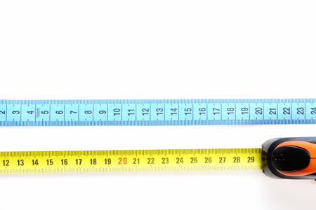 Sorts of measuring tapes: cyan sewing ruler of cloth and self retracted yellow ruler of plastic and metal, isolated on white background with copy space, top view Imagens