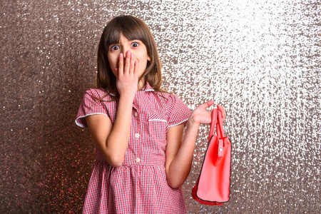 small pretty girl or cute fashionable child with long brunette hair and adorable surprised happy face in checkered dress with female red leather bag on metallic silver background, copy space