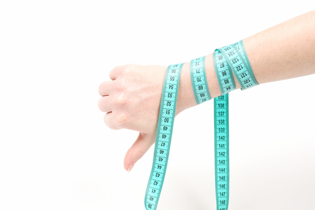 tied down: Hand of young woman with thumb down and arm tied around with cyan measuring tape, isolated on white background