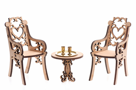 Goblets on golden tray on decorative engraved wooden table with chairs isolated on white background, copy space. Antique concept