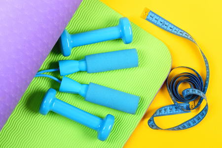 Sports for body. Blue skipping rope and dumbbells lying on green yoga mat and rolled measuring tape nearby isolated on yellow background, top view. Health and fitness concept