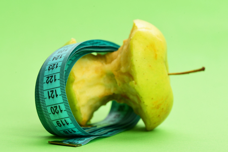 Concept of diet, vitamin nutrition and healthy lifestyle: bitten apple lying on side wrapped with greenish blue flexible ruler on light green background