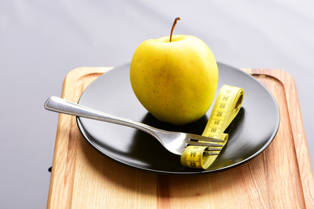 Apple and fork which has measuring tape between its tines. Items lying on black plate standing on vintage wooden cut board on light grey background