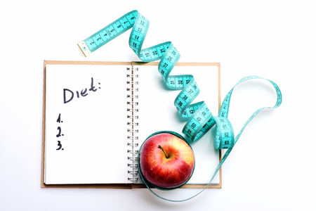Notebook with diet plan and twisted blue measuring tape on it tied around red apple isolated on white background, top view and copy space. Healthy nutrition and regime concept