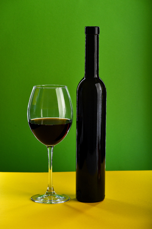 Wine in glass and bottle on yellow surface and on green background