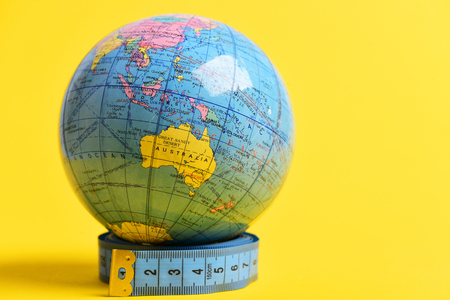 Globe model standing on roll of blue measuring tape isolated on yellow background with copy space. Visible hemisphere which contains Australia on it Stock Photo