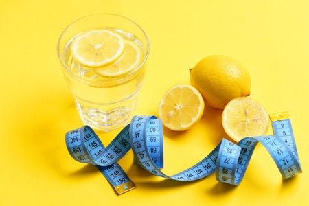 Diet concept. blue meter tape, lemon with freshly squeezed glass of citrus on yellow background