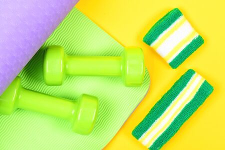 Dumbbells on green and purple mat for yoga and sweatband with wristband isolated on yellow background, top view Reklamní fotografie