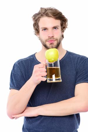 Apple van groene kleur bovenop bierglas in macho bemant hand, die op witte achtergrond wordt geïsoleerd. Concept keuze tussen gezonde levensstijl en alcohol