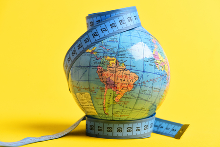Globe wrapped with measuring tape on its poles, isolated on warm yellow background. Symbol of globalization and worldwide population growth