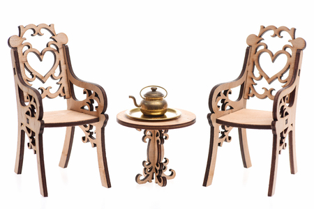 teapot on decorative wooden table with engraved chair isolated on white background. Antique concept Stock Photo