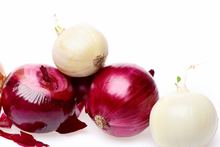 Group of red and white onions lying on each other with some dry peel underneath and peeled onion with little sprout in its tail isolated on white background, close up. Healthy eco food concept