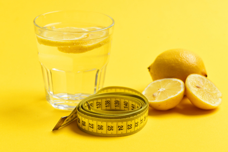 vaso de precipitado: meter tape, lemon with freshly squeezed glass of citrus on yellow background. Nutrition and diet concept