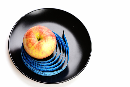Apple and blue tape for measuring on black ceramic plate, isolated on light grey background. Vitamin diet concept