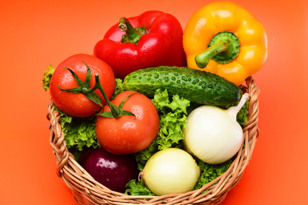 healthy nutrition concept, vegetables or green lettuce leaf, tomatoes with onions, peppers, cucumber in basket isolated on orange background