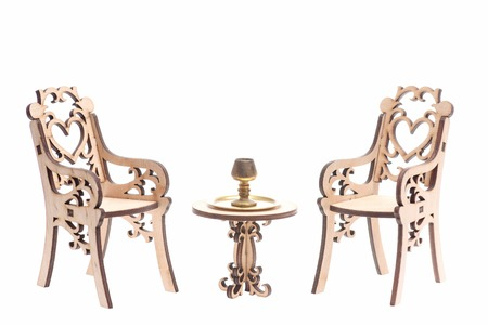 Chalice on golden stray on vintage table with engraved chairs isolated on white background, copy space