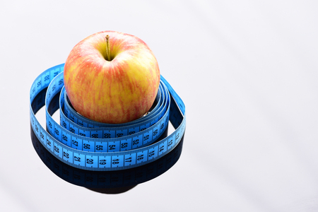 Tape for measuring wraps around red ripe apple on light grey surface with copy space. Vitamin diet and weight management concept