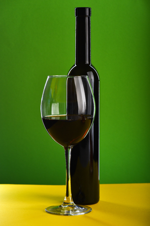 Glass filled with red wine near dark bottle standing on yellow surface on green background