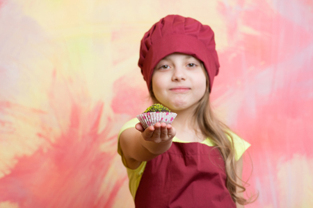 poquito: child or happy little girl cook in red chef hat and apron eating cupcake on colorful abstract background, cooking and food