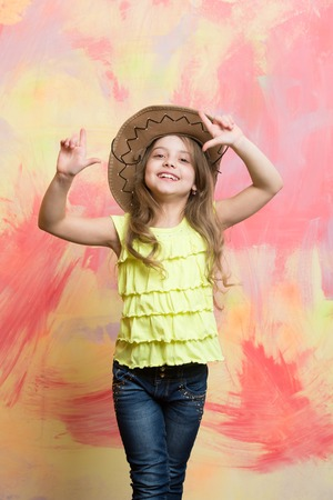 happy child or little girl in cowboy hat with smiling cute face and raised hands on colorful background