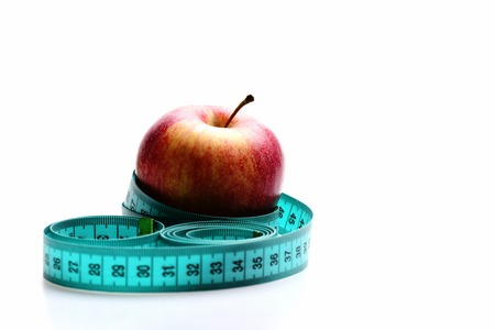 Concept of healthy lifestyle and fruit diet: red apple wrapped with cyan tape for measuring, isolated on white background with copy space Stock Photo