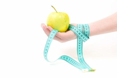 Hand with green apple and cyan measuring tape, which wraps around wrist, isolated on white background Stock Photo