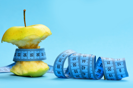 Apple bitten and tied around with blue measuring tape twisted at the ends on blue background, close up and copy space. Diet and fitness concept