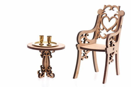 Goblets isolated on white on golden tray on decorative engraved wooden table and chair, copy space