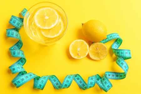 Lemon and tape. Concept of healthy lifestyle with whole citrus, several slices and lemon water twisted around with cyan flexible ruler, isolated on yellow background. Top view Reklamní fotografie