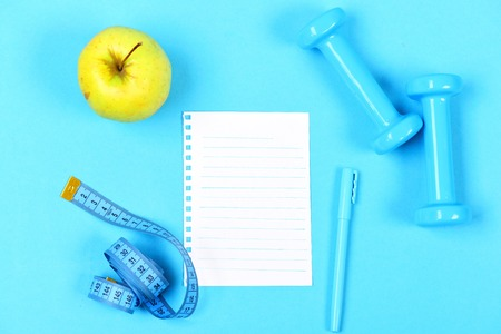 Dieting and regime concept with blank white notebook page, light blue pen, dumbbells and measuring tape near juicy green apple isolated on bright blue background, top view and copy space Stock Photo