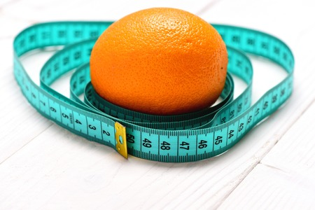 Orange fruit in the middle of turquoise measuring tape circles on white wooden background, close up and selective focus. Healthy nutrition and slim shape concept Stock Photo