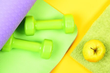Yoga mat of purple and green colours with dumbbells and green apple on towel isolated on yellow background, top view. Concept of healthy lifestyle