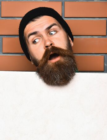 brutal: Bearded man, long beard. Brutal caucasian surprised unshaven hipster in black hat with white paper sheet on brown brick wall studio background, copy space