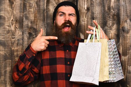 brutal: Bearded man, long beard. Brutal caucasian happy hipster with moustache holding shopping packages in red black checkered shirt on brown wooden vintage studio background