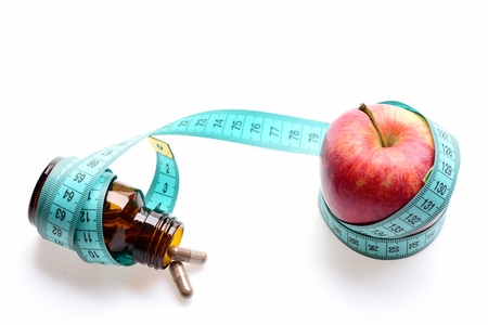 Concept of vitamins, diet and nutrition: red apple and bottle with pills wrapped around with greenish blue measuring tape, isolated on white background