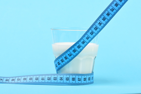 Tape for measuring wraps around glass of milk, isolated on light blue background