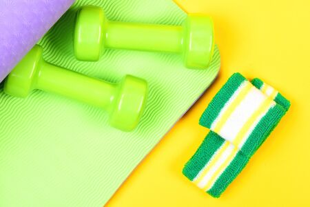 Fitness and health. Lightweight dumbbells lying on green and purple yoga mat near headband and wristband isolated on yellow background, top view